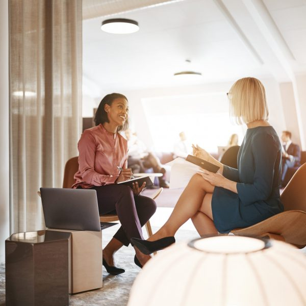 two-smiling-businesswomen-having-a-meeting-togethe-9VBRDNU-scaled.jpg